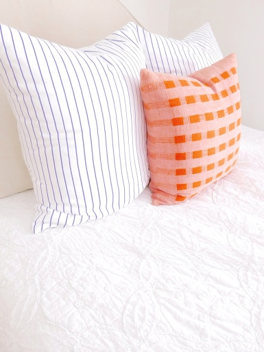 Pillows from Serena & Lily add intrigue to neutral bed linens.